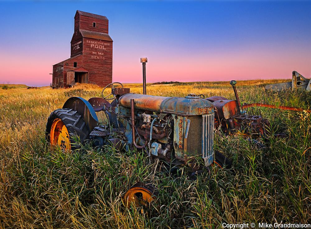 Grain elevator with old tractor at dawn<br /> Bents<br /> Saskatchewan<br /> Canada