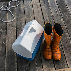 Rubber boots and a lunch cooler on the wharf at the Friendship Lobster co-op in Friendship, Maine.
