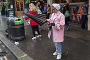 A stylish lady in pink adjusts her umbrella in St. Martins Lane, Westminster, on 9th April 2019, in London, England.