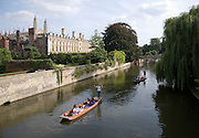 People punting in small boats on the River Cam, Cambridge England with Clare College in the background