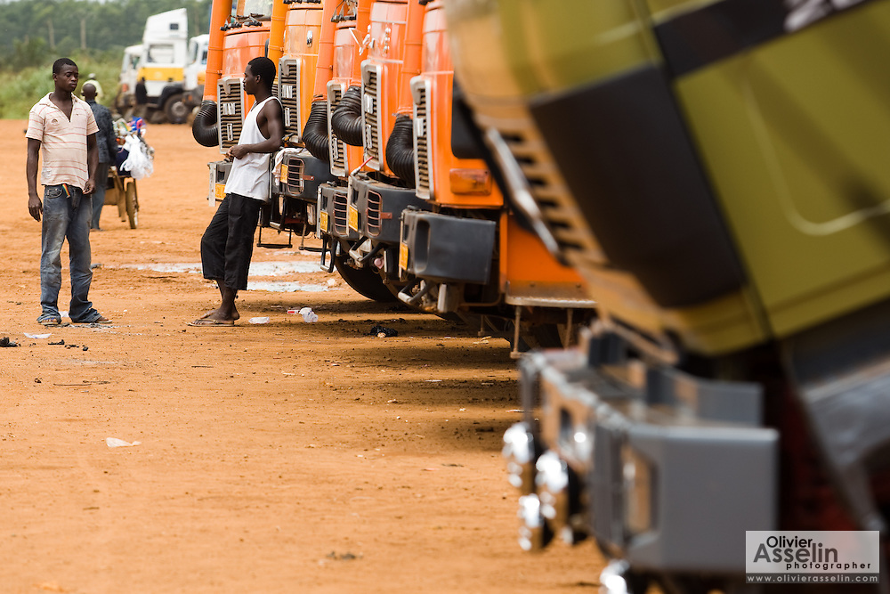 Men stand by a row of large trucks parked at the Terminal du Sahel, a large truck terminal in Lome, Togo on Wednesday October 1, 2008.