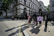 "Two protestors banners say ""People Say Sack"" and ""Take back Control, Sack him Now!"" outside Downing Street, in London, as the row over Prime Minister Boris Johnson's top aide Dominic Cummings' Durham trip, continues on Wednesday, May 27, 2020. The prime minister's populist appeal has been hammered by the news that, as the coronavirus outbreak raged, chief adviser Cummings drove 250 miles (400 kilometres) to his parents' house while he was falling ill with suspected COVID-19 allegedly flouting lockdown rules that the government had imposed on the rest of the country. (Photo/ Vudi Xhymshiti)"