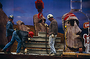 Construction workers wearing hard hats hook up a pile of concrete beams on to a waiting crane hook. One man bends down to help loop a chain beneath one of the girders and attached to the dangling hook while another secures the chain and another man is in radio contact with the crane driver out of sight. Importantly, behind their low-loader truck is a Smirnoff advertising billboard with a famous ad campaign for the Vodka distillery. It depicts three carved Polynesian statues of Easter Island but seen through a botttle of the alcoholic beverage, is a representation of a face wearing a head band and MP3 headphones. Seen juxtaposed with the construction men and their building technology this scene describes a visual pun between an ancient lost civilization and the modern age of technology. Smirnoff is a vodka distillery founded in Moscow, by Piotr Arsenieyevich Smirnov. The <br /> brand is now distributed in 130 countries and includes flavored vodka and malt beverages. The Sminoff advertising campaign is said to be based on the Belgian surrealist artist Rene Magritte whose paradoxical images stretched our ideas of what was reality and the fantastic.