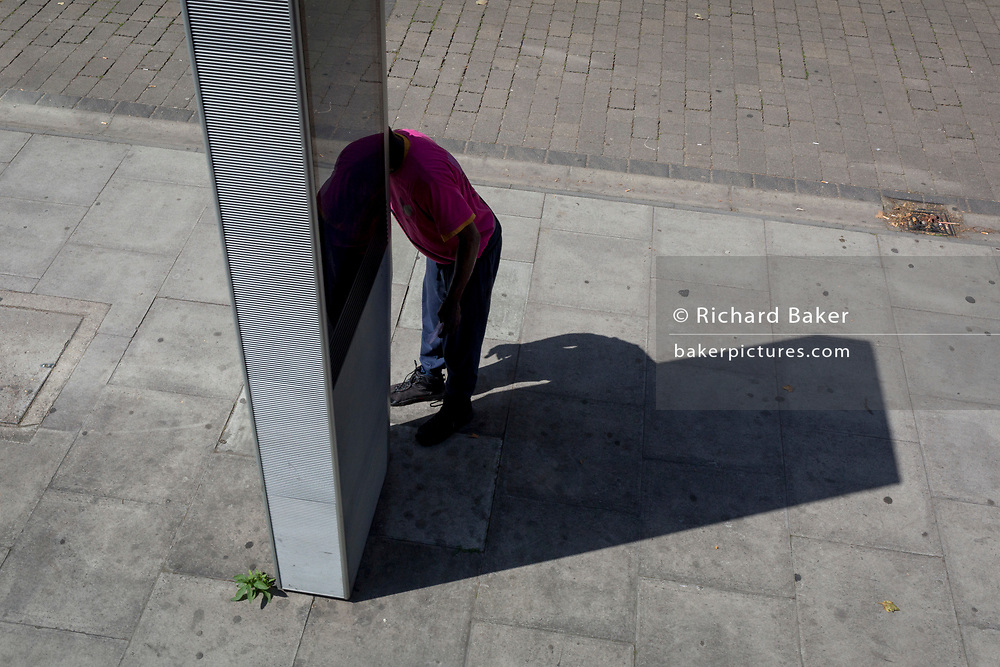 An anonymous man uses a free street phone service on the Walworth Road, on 25th July 2019, in London, England. (Photo by Richard Baker / In Pictures via Getty Images)