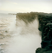 Ocean waves smash onto cooled lava rock in A man photographs a lava flow in Hawaii Volcanoes National Park, Hawaii, USA