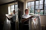 Priest puts on his Alb before morning Mass in Sacristy (Vestry) at St. Lawrence's Catholic church in Feltham, London.
