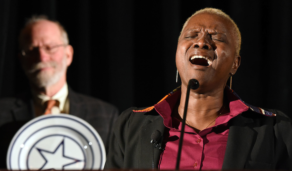 """Photo by Mara Lavitt -- Special to the Hartford Courant<br /> Omni New Haven Hotel at Yale, New Haven, CT<br /> January 28, 2015<br /> Grammy Award-winning singer and UNICEF Goodwill Ambassador Angelique Kidjo was the International Festival of Arts & Ideas 5th annual Visionary Leadership Award recipient. Gordon Geballe, chair of the Festival's board of directors, holds the award -- a plate designed by artist Sol Lewitt -- as Kidjo sings """"Blewu"""" after receiving the award. Kidjo is co-founder of the Batonga Foundation which advocates for the rights of women and girls, especially in Africa."""