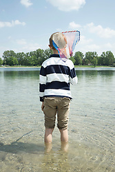 Rear view of a boy holding a brailer in the lake, Bavaria, Germany