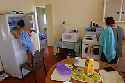 (MODEL RELEASED IMAGE). 5-year old Sinead Brown gazes into her family's nearly-empty freezer in the kitchen of their rented home in Riverview, Australia (near Brisbane). Every two weeks a new check appears and the family goes to the supermarket. Sinead's mother Vanessa is cooking at the stove. (Supporting image from the project Hungry Planet: What the World Eats.)