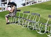 © licensed to London News Pictures. EPSOM, UK.  03/06/11. A woman reads the race programme on a bench. Epsom Derby Ladies Day. Sunshine and wind made for a busy Ladies Day today, 3rd June 2011.  Photo credit should read Stephen Simpson/LNP