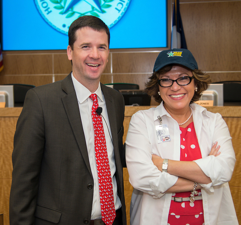 Dr. Andrew Houlihan, left, presents Rodriguez Elementary School principal Elena Martinez-Buley, right, with a Team HISD cap, June 11, 2014.