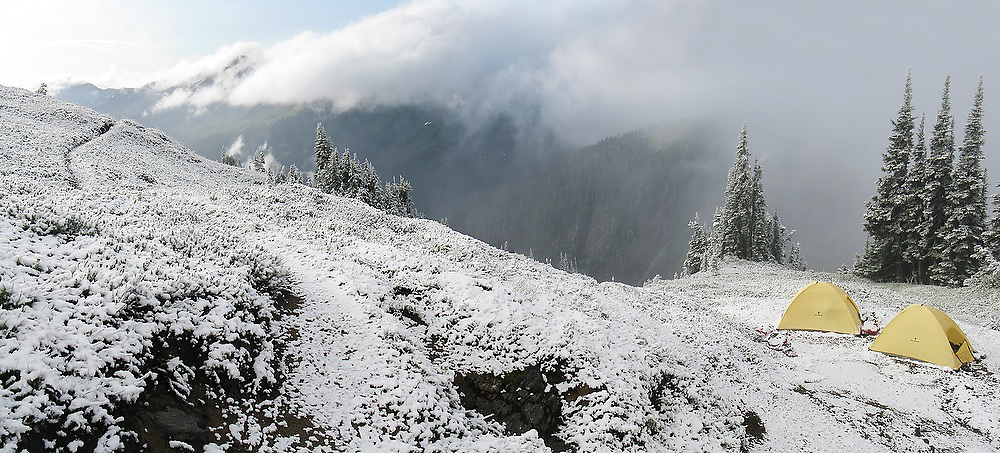 Tents covered in snow besides a trail in Glacier Peak Wilderness, Washington.
