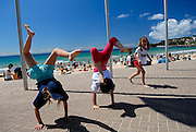 Three children (two 10 year olds, one 6 year old) doing handstands on Manly Beach concourse. Manly, Sydney, Australia