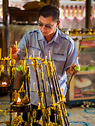 """30 DECEMBER 2017 - BANG KRUAI, NONTHABURI, THAILAND:  A man lights prayer candles to make merit for the new year at Wat Ta Khien, about 45 minutes from Bangkok in Nonthaburi province. The temple is famous for the """"floating market"""" on the canal that runs past the temple and for the """"resurrection ceremonies"""" conducted by monks at the temple.      PHOTO BY JACK KURTZ"""