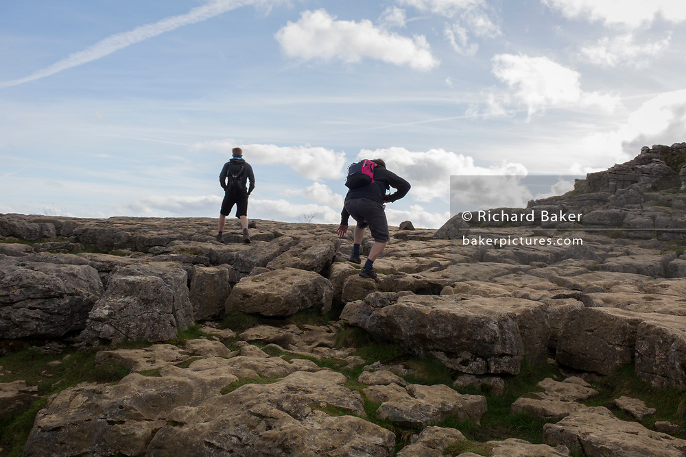 Walkers pass over the limestone pavement at Ing Scar near Malham in the Yorkshire Dales National Park, on 12th April 2017, in Malham, Yorkshire, England. A limestone pavement is a natural karst landform consisting of a flat, incised surface of exposed limestone that resembles an artificial pavement. The term is mainly used in the UK where many of these landforms have developed distinctive surface patterning resembling paving blocks.