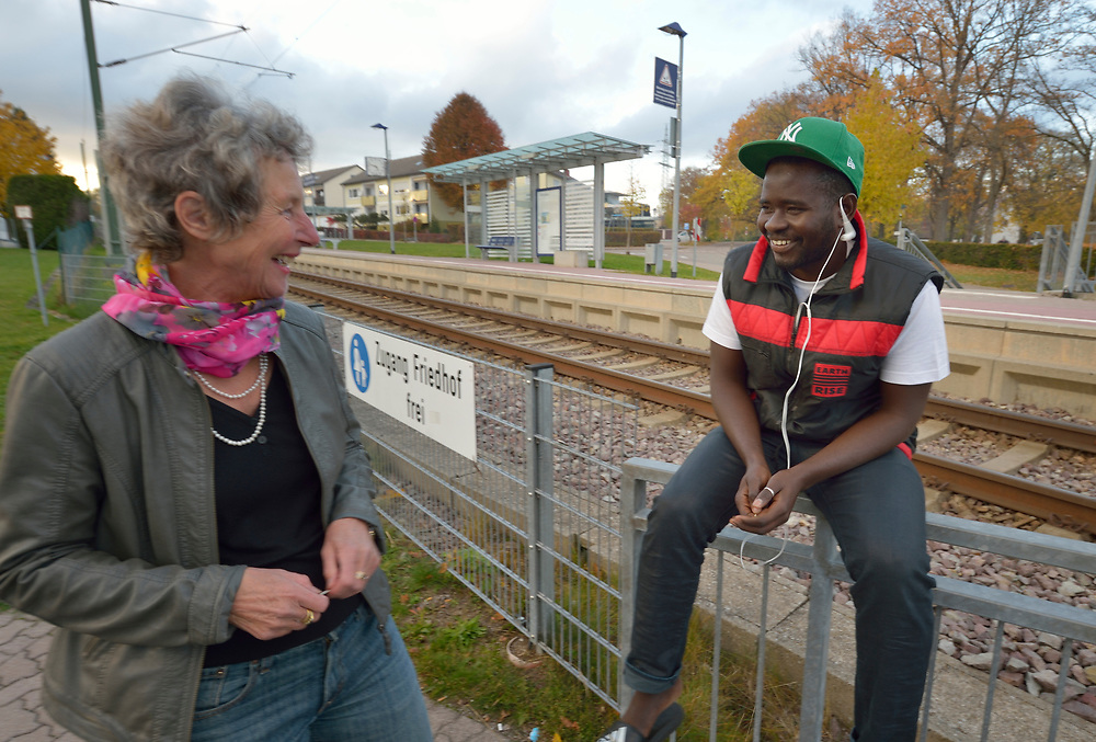 Baboucarr Ellsay, 20, an asylum seeker from Gambia, talks with a neighbor outside the church-run shelter where he lives in Freudenstadt, Germany. The Freundesdreis Asyl is run by Christlicher Kirchen, and managed by a retired United Methodist pastor. The shelter has 18 asylum seekers from Eritrea and 10 from Gambia. They came to Europe via Sudan and Libya, crossing the Mediterranean to Italy.