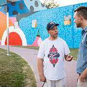 """Former Hagerstown Mayor, David Gysberts, right, speaks with Herman """"Skip"""" Davis near a gigantic mural painted on the side of a former grain mill in downtown Hagerstown, Maryland, on Tuesday, September 26, 2017. The mural was the last contract that Gysberts signed before leaving office last year. Originally a District that was mostly rural, but included towns like Frederick and Hagerstown, Maryland's 6th District was redistricted in 2011, combining rural northern Maryland regions with more affluent communities like near Washington D.C. turning the district from Republican to Democrat. <br />  <br /> CREDIT: John Boal for The Wall Street Journal<br /> GERRYMANDER"""
