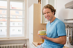 Smiling man with cup of coffee in kitchen
