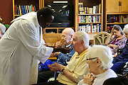 Rev. Paula Maina Waithaka offer communion to residents at The Abbington of Glenview healthcare residence on Wednesday, August 20th. Waithaka is Pastor at St. Catherine Laboure in Glenview. August 20th, 2014 l Brian J. Morowczynski-ViaPhotos<br /> <br /> For use in a single edition of Catholic New World Publications, Archdiocese of Chicago. Further use and/or distribution may be negotiated separately. <br /> <br /> Contact ViaPhotos at 708-602-0449 or email brian@viaphotos.com.
