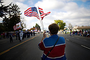 A woman waves two flags while taking a photo at the Veterans Day parade in Elk Grove, California on Nov. 11, 2007.