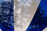 Trees seen through a sheer canopy tarp providing shade at an event.