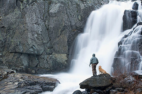 Young man fly fishing on river during storm near South Lake Tahoe, CA..Release code: 050