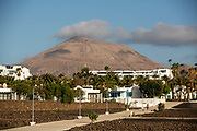 A woman walks her dog in the shadow of a volcano in Playa Matagorda, Lanzarote, Spain on 22nd November 2020. Beaches and resorts across the island are nearly deserted since tourism plummeted due to Covid restrictions elsewhere in Europe. Although the Canary Islands have been relatively unscathed by the virus, with 155 lives lost from 2.1 million residents, the region is heavily dependent on tourism and locals are hoping that numbers recover as lockdown measures ease and vaccines potentially reduce the numbers of infections.