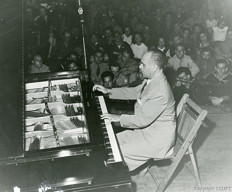 1944 Pianist, Jose Iturbi plays the piano for the audience at the Hollywood Canteen.