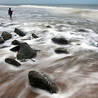 Water rolling over rocky shoreline of Sandy Hook as a fisherman fishing the fall fishing season for Striped Bass and Bluefish.  Sandy Hook it part of the Gateway National Recreation area New Jersey