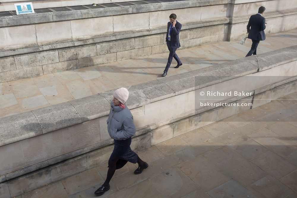 A lady strides down Whitehall and two men are separated by a wall, on 28th October 2019, in Westminster, London, England.