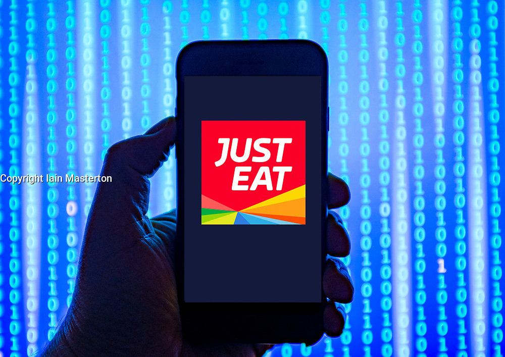 Person holding smart phone with  Just Eat food delivery service logo displayed on the screen. EDITORIAL USE ONLY