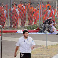 072315       Cable Hoover<br /> <br /> Inmates watch as law enforcement and emergency medical personnel tend to one of their fellow inmates during a disturbance at the McKinley County Detention Center Thursday.