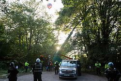 Wendover, UK. 10th October, 2021. A hot air balloon passes over enforcement agents from the National Eviction Team (NET) and Thames Valley Police officers taking part in the first day of an operation to evict environmental activists opposed to the HS2 high-speed rail link from Wendover Active Resistance (WAR) camp. WAR camp, which contains tree houses, tunnels, a cage and a 15-metre tower, is currently the largest of the protest camps set up by Stop HS2 activists along HS2's Phase 1 route between London and Birmingham.