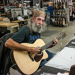 A musician testing a new guitar at the Martin Guitar Company in Nazareth, Pennsylvania.