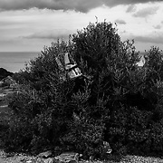 A migrant life jacket can be seen stuck on a bush as Mantamados villagers clash with police in protest of a new proposed migrant detention camp in Mantamados on the Greek Island of Lesvos on Wednesday, February 26, 2020. Credit: Byron Smith