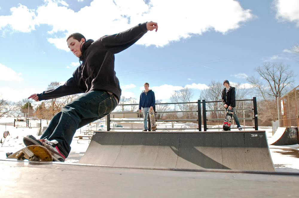"""Matt Dixon   The Flint Journal..Brian Goss, 17, skates while Brett Stiefel (left), 19, and Bo Cook, 20, watch. The three removed snow from the half pipe over the past few days so they could finally skate. """"We try to skate as much as possible. Winter time. Spring time. Summer time. Anytime."""" said Stiefel."""
