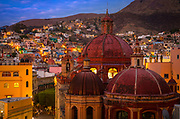 View from the hills above Guanajuato, Mexico, overlooking the historical center of the city.<br /> ------<br /> Guanajuato is a city and municipality in central Mexico and the capital of the state of the same name. It is part of the macroregion of Bajío. It is in a narrow valley, which makes its streets narrow and winding. Most are alleys that cars cannot pass through, and some are long sets of stairs up the mountainsides. Many of the city's thoroughfares are partially or fully underground. The historic center has numerous small plazas and colonial-era mansions, churches and civil constructions built using pink or green sandstone.<br /> <br /> The origin and growth of Guanajuato resulted from the discovery of minerals in the mountains surrounding it. The mines were so rich that the city was one of the most influential during the colonial period. One of the mines, La Valenciana, accounted for two-thirds of the world's silver production at the height of its production.<br /> <br /> The city is home to the Mummy Museum, which contains naturally mummified bodies that were found in the municipal cemetery between the mid 19th and 20th centuries. It is also home to the Festival Internacional Cervantino, which invites artists and performers from all over the world as well as Mexico. Guanajuato was the site of the first battle of the Mexican War of Independence between insurgent and royalist troops at the Alhóndiga de Granaditas. The city was named a World Heritage Site in 1988.