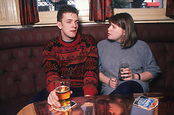 Couple sitting at table in pub drinking and talking,