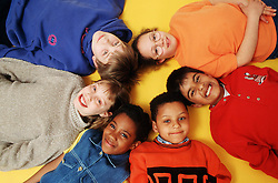 Multiracial group of children lying in circle smiling,