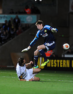 Michu scores for Swansea City as Kuban Krasnodar goalkeeper Aleksandr Belenov jumps over him.<br /> UEFA Europa league match, Swansea city v FC Kuban Krasnodar at the Liberty Stadium in Swansea, South Wales on Thursday 24th October 2013. pic by Phil Rees, Andrew Orchard sports photography,
