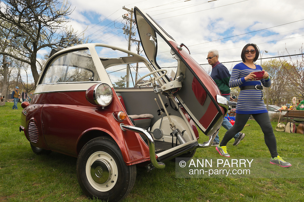 Floral Park, New York, U.S. - April 27, 2014 - Visitors look at the 1958 BMW Isetta 300 at the 35th Annual Antique Auto Show at Queens Farm. Designed by the Italian refrigerator company ISO, it has a refrigerator-like front door which swings open to let the driver and passenger enter.