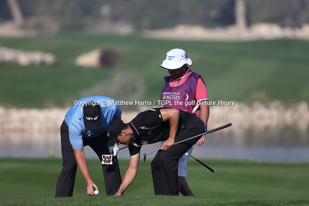 Peter HANSON (SWE) and Martin KAYMER (GER) sort out  marking Hanson's ball as their balls were very close together during second round Commercialbank Qatar Masters 2014,Doha Golf Club,Doha,Qatar.