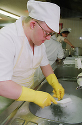 Man with Downs Syndrome washing up in kitchen,