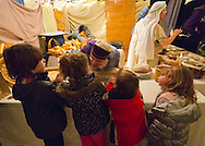 Garden City, New York, USA. December 6, 2013. At the Bakery Store at A Night in Bethlehem, visitors experience what it might have been like the night Jesus was born. Families visit different shops and participate in projects. Finally the children and adults experience the nativity scene at the manger, with Mary, Joseph, and baby Jesus, on the first Christmas. This free annual Advent event is December 6, 7, and 8, at the Lutheran Church of the Resurrection, on Long Island.