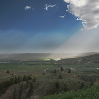 The sun illuminates dust blowing off plowed dry land fields in the Upper Missouri River Breaks of central Montana.