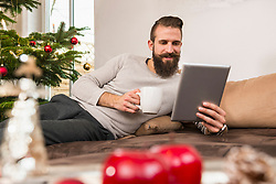 Man using digital tablet and having coffee at home