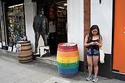 Woman on Old Compton Street in Soho checks her phone outside a bottle shop with a cut out leather clad figure in the doorway in London, United Kingdom. This area is known as the gay capital of London.