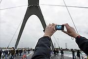 Nederland, Nijmegen, 24-11-2013Zaterdag is de nieuwe stadsbrug van de stad Nijmegen, de Oversteek, in gebruik genomen, geopend. Op de foto neemt het publiek zondag de brug in bezit. Na middernacht mogen de autos er op.  Ongeveer 10.000 mensen liepen naar de andere kant en terug. Dit gebeurde door het in twee jeeps afrijden van de brug van Zuid naar Noord door de twee enige nog levende veteranen van de oversteek in 1944. De brug is vernoemd naar de heldhaftige oversteek van de rivier de Waal die Amerikaanse soldaten op dit punt maakten tijdens de operatie Market Garden in de tweede wereldoorlog om met succes de oude Waalbrug te veroveren. De overspanning is een belangrijke schakel in de ontlasting van de stad van het doorgaande verkeerDe Oversteek is een boogbrug van 285 meter lang en 60 meter hoog en is de op een na langste hoofd overspanning van Nederland, en de grootste boogbrug van Europa met een enkelvoudige boog.De brug wordt 23 november in gebruik genomen.De nieuwe oeververbinding moet zorgen voor een betere spreiding en doorstroming van verkeer binnen de stad Nijmegen. Na 75 jaar is er eindelijk een tweede vaste verbinding voor de stad. De oude waalbrug krijgt vanaf eind dit jaar groot onderhoud, waarna de volle capaciteit van beide bruggen pas gebruikt kan worden. De skyline van de stad is veranderd.De brug is een ontwerp van de Belgische architecten Ney en Paulissen. Foto: Flip Franssen/Hollandse Hoogte