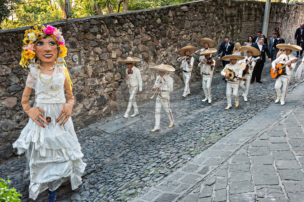 A traditional Mexican mariachi band plays as giant puppets called mojigangas dance during a wedding celebration parading through the streets San Miguel de Allende, Guanajuato, Mexico.