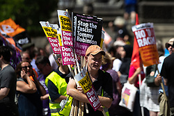"""© Licensed to London News Pictures . 07/07/2018 . Leeds , UK . Anti Fascist counter-protesters hand out placards during an anti-Islam demonstration by supporters of jailed EDL founder Tommy Robinson , including those from the """" Yorkshire Patriots """" and """" First for Britain """" , in Leeds City Centre . Robinson ( real name Stephen Yaxley-Lennon ) was convicted of Contempt of Court in May 2018 after committing a second offence , whilst serving a suspended sentence for the same crime . Photo credit : Joel Goodman/LNP"""